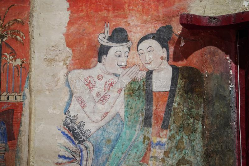 Den vägg- målningen för famousav en man som viskar till theörat av en kvinna på Wat†‹Phumin royaltyfri bild
