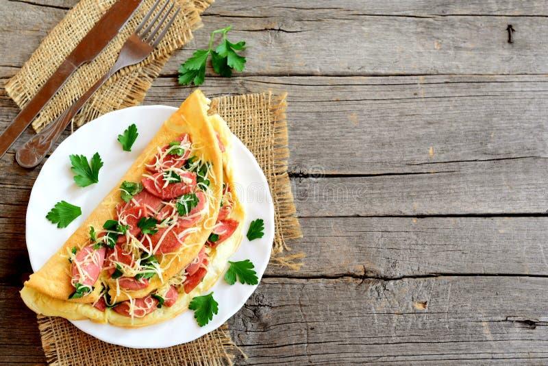 Den välfyllda omelettet med stekte korvar, grated ost och persilja på en platta, dela sig, baktalar på en gammal träbakgrund med  arkivfoto
