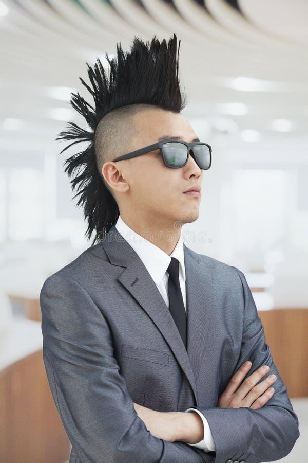 Den välklädda unga mannen med Mohawk och solglasögon, armar korsade i kontoret arkivfoto