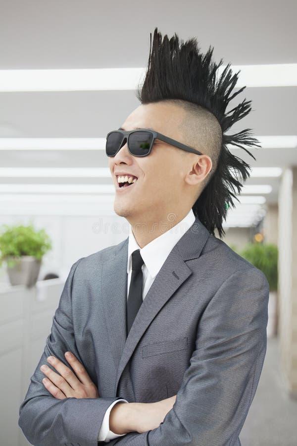 Den välklädda unga mannen med Mohawk och solglasögon som ler, armar korsade i kontoret royaltyfri fotografi
