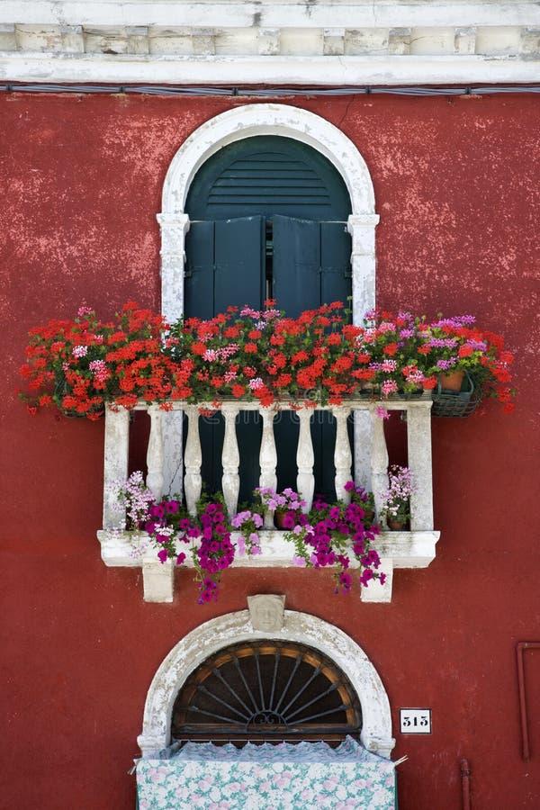 den välvda balkongen blommar fönstret royaltyfri fotografi