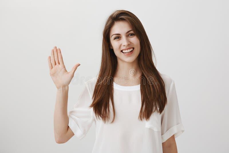 Den vänliga kvinnan säger högt till nya grannar Stående av den charmiga unga känslobetonade kvinnan som vinkar med den lyftta han royaltyfri foto