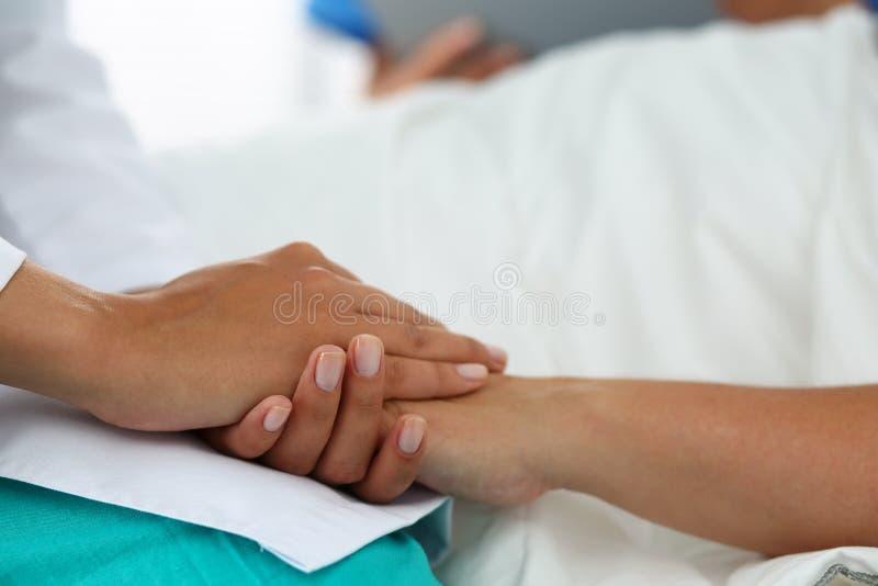 Den vänliga kvinnliga doktorn räcker den hållande tålmodiga handen arkivbild