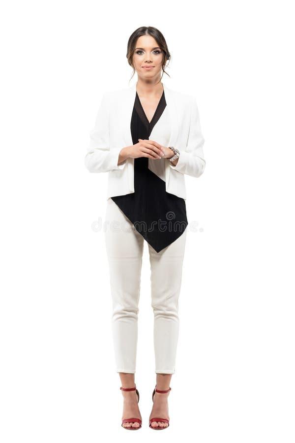 Den vänliga le kvinnliga presentatören för affären i formell dräkt med händer knäppte fast att se kameran royaltyfri fotografi
