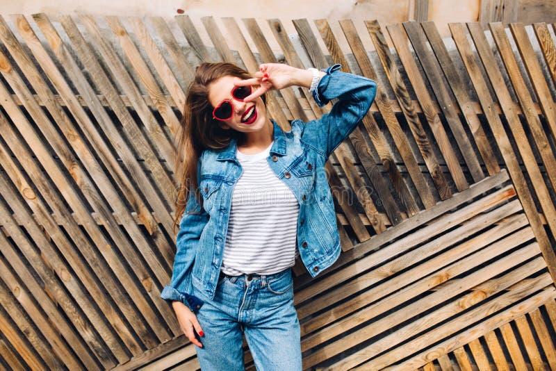 Den vänliga skratta flickan i jeans passar göra ett fredtecken Le den kvinnliga modellen i den randiga tröjan som poserar bredvid royaltyfria bilder