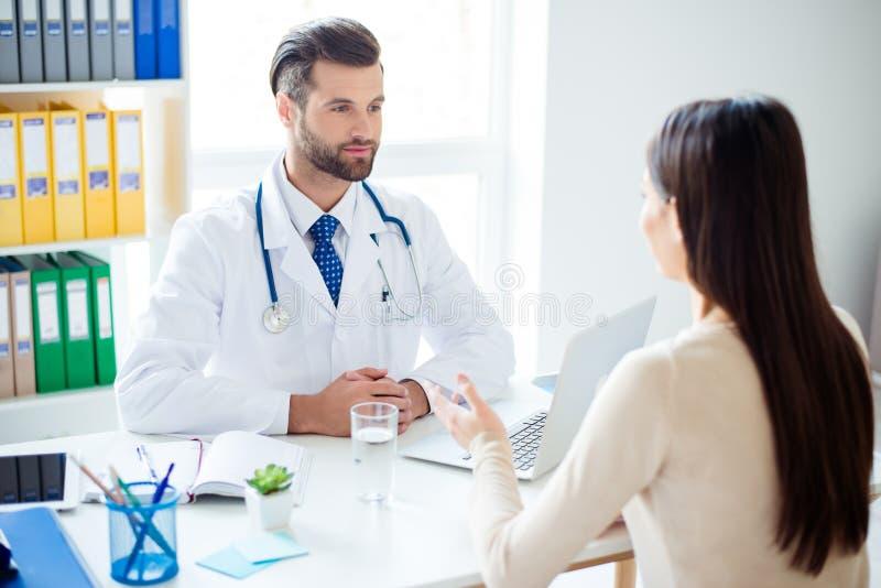 Den vänliga unga stilfulla doktorn konsulterar brunettkvinnligpatienten royaltyfri foto