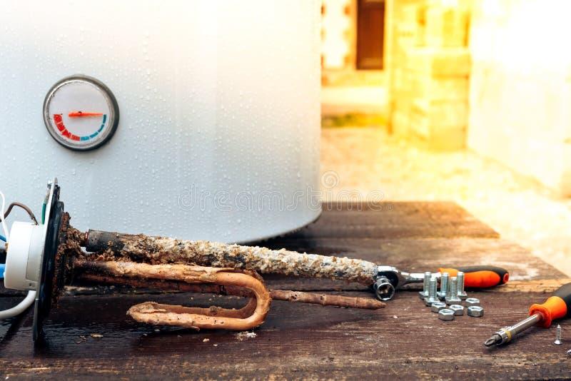 Den värma beståndsdelen täckas med rost och skalan, med skruvar på bakgrunden av kokkärlet som ligger på en trätabell arkivfoto