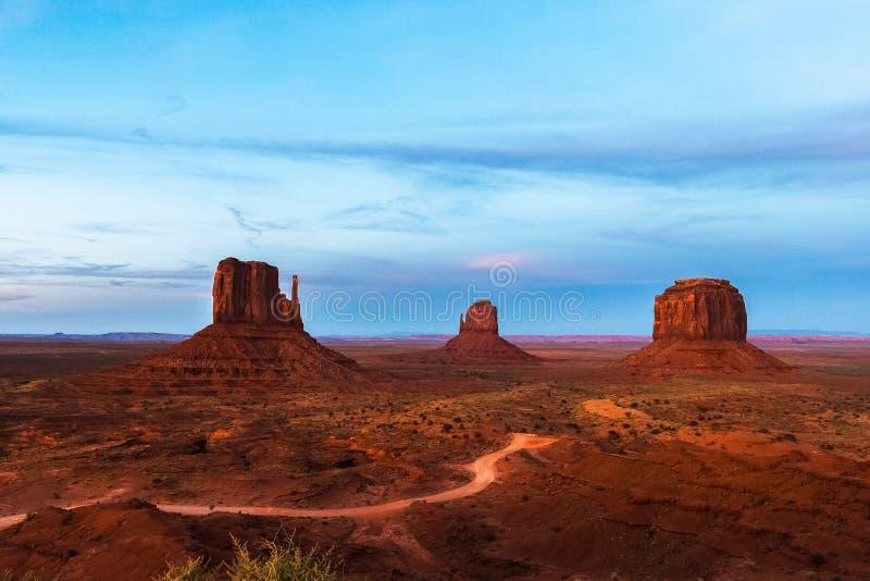 Den västra och östliga tumvantet och Merrick Buttes i den stam- monumentdalnavajoen parkerar på skymning, Arizona royaltyfria foton