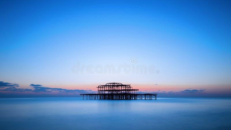 Den västra pir av Brighton efter solnedgång, England, UK royaltyfri foto