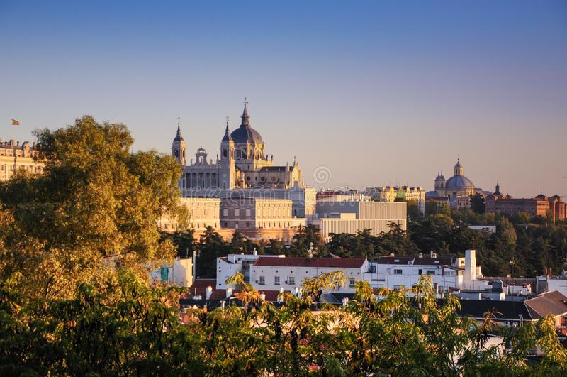 Den västra vingen av Royal Palace av Madrid och domkyrkan av Santa María la Real de la Almudena exponerade med solnedgångsikt frå royaltyfria foton