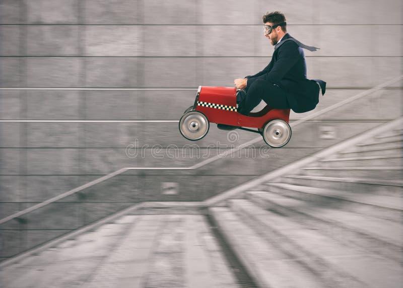 Den våghalsiga affärsmannen går ner trappan med en bil att få för andra Begrepp av framgång och konkurrens arkivfoton