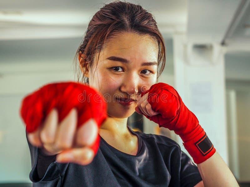 Den valda fokusen av unga härliga kvinnor bär ett rött thailändskt boxas band som är klart för att stansa royaltyfria bilder