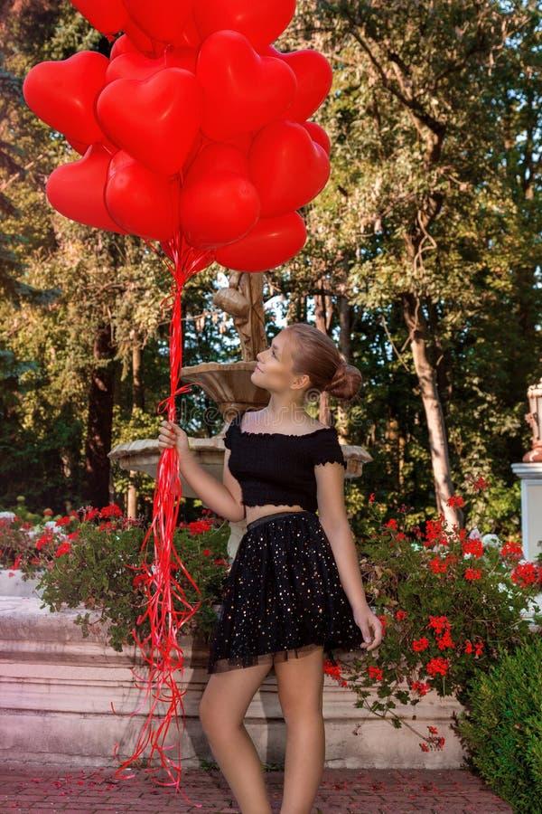 Den Valentine Beautiful unga flickan med rött ballongskratt, i parkerar Härlig lycklig unge Tre nätt sexiga flickor som slitage S royaltyfri foto