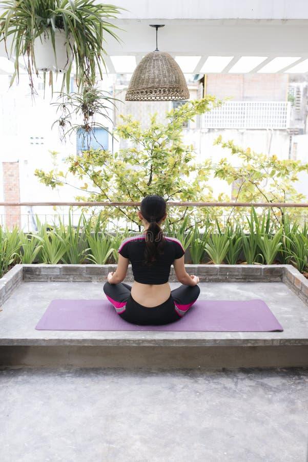 Den ?vande yogan f?r h?rlig kvinna p? en filt och sitta p? en balkong royaltyfri bild