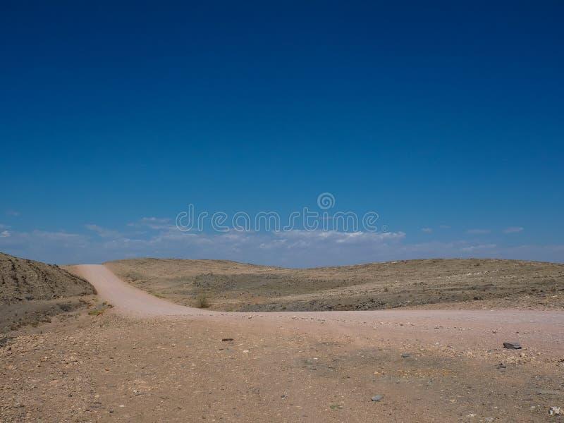 Den varma härliga dagen på affärsföretagvägtur till och med öken vaggar berglandskaprutten till tomhet med bakgrund för blå himme royaltyfri bild