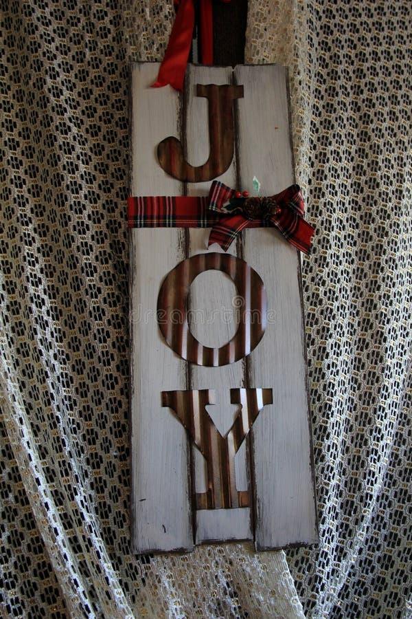 Den varma platsen med gammalmodig jul undertecknar med ordet GLÄDJE i målat trä arkivfoton