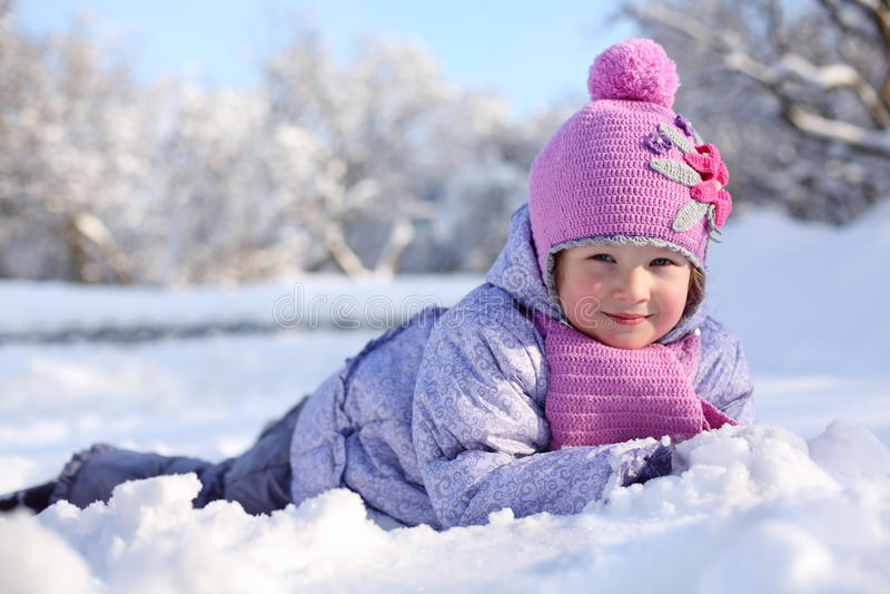 Den varmt klädde lilla lyckliga flickan i rosa halsduk och hatt ligger arkivfoto