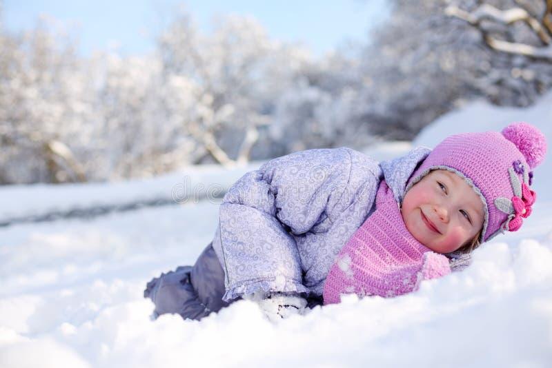 Den varmt klädde lilla lyckliga flickan i rosa halsduk och hatt ligger arkivbild