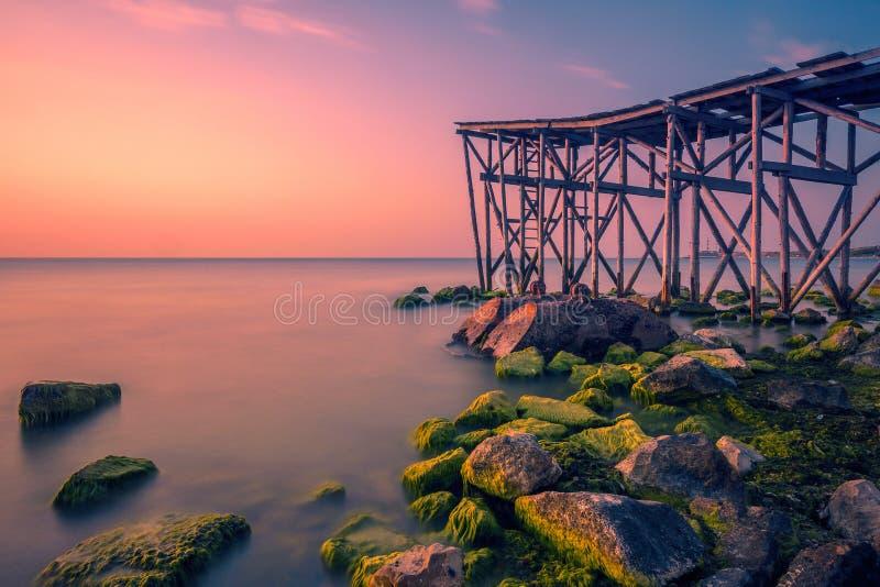 Den varmt morgonen på sjösidan på soluppgång med en pir på kusten och härligt vaggar täckt med alger royaltyfria foton