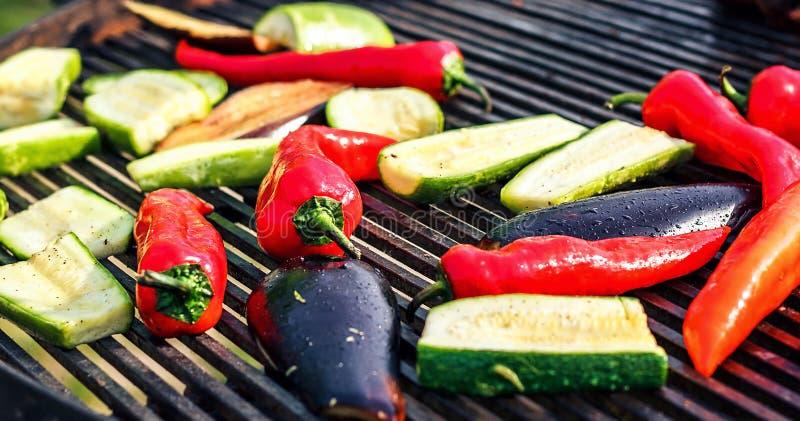 Den vegetariska grillfesten med zucchinin, röd peppar, aubergine, grillade över kol Grönsaker på gallret över sparlåga royaltyfria foton