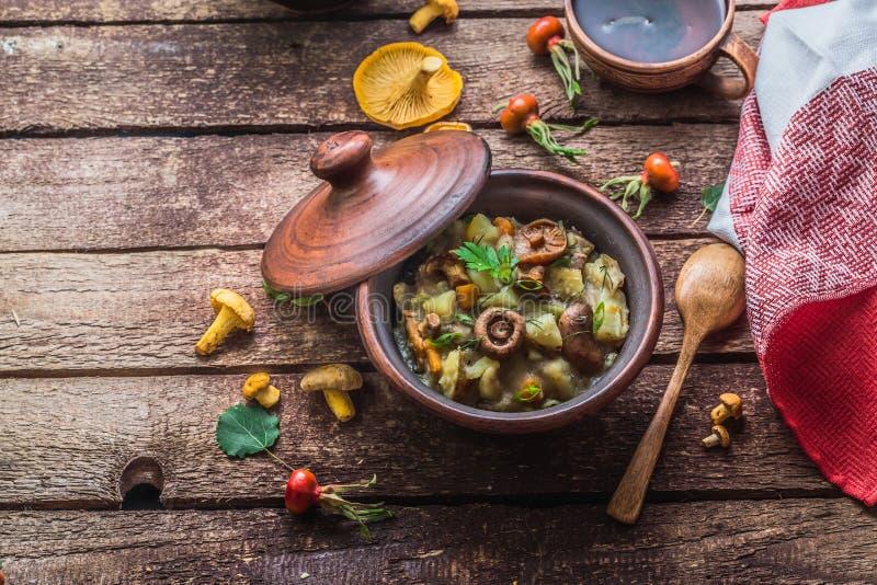 Den Vegeterian potatisen och champinjoner låter småkoka i en lerakruka, kopieringsutrymme arkivbilder