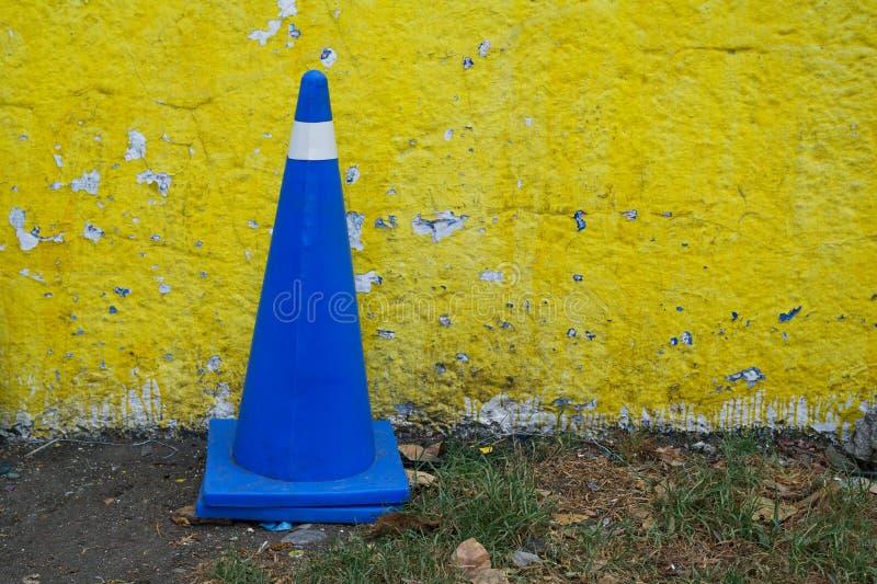 Den Vehicular kontrollkotten i kungliga blått färgar mot en gul vägg royaltyfri fotografi