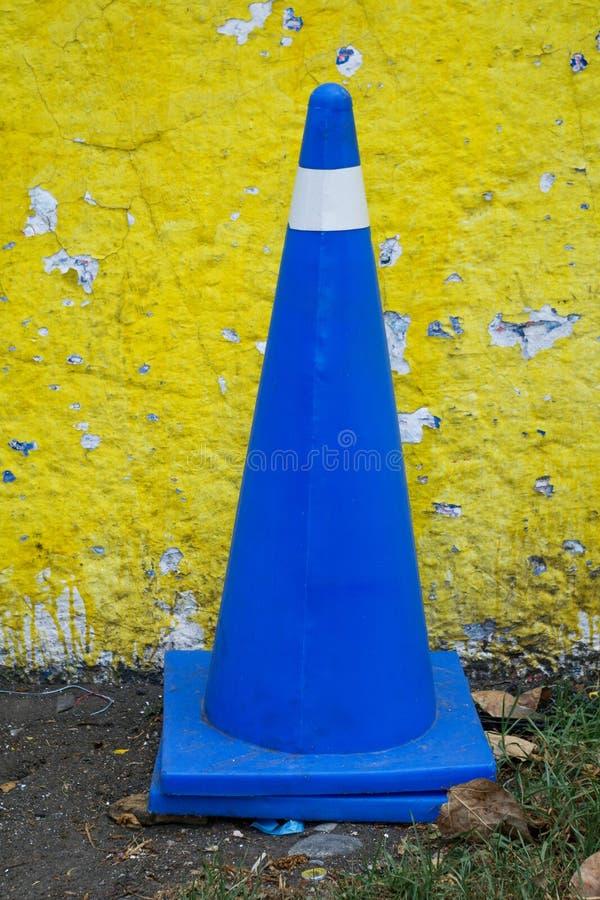 Den Vehicular kontrollkotten i kungliga blått färgar mot en gul vägg royaltyfri foto