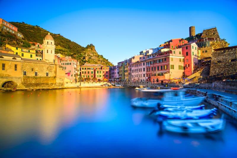 Den Vernazza byn, kyrkan, fartyg och havet härbärgerar på solnedgång Cinque royaltyfri bild