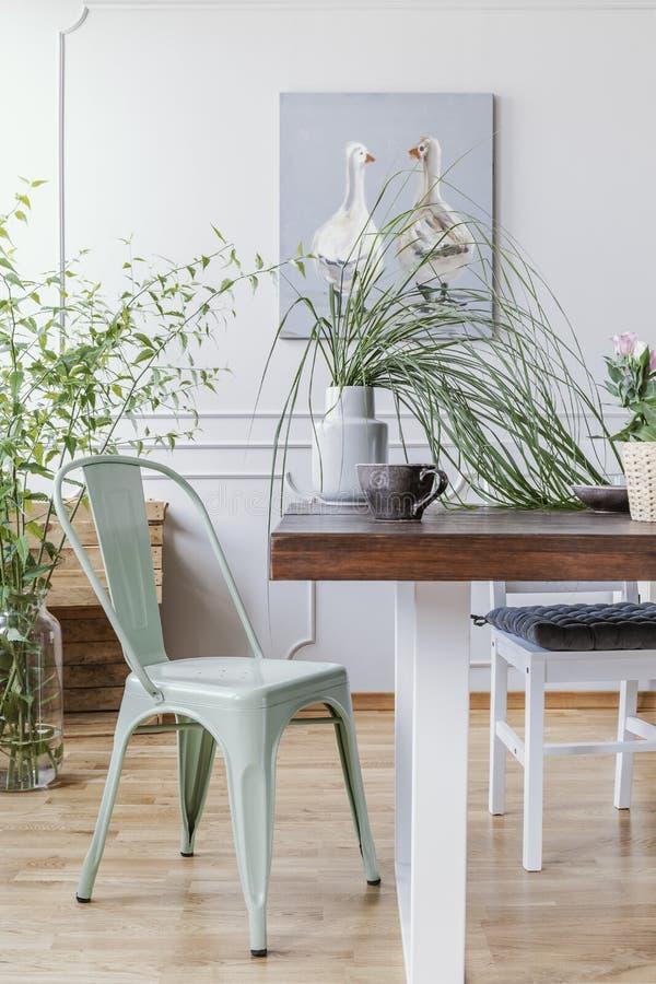 Den vertikala sikten av mintkaramellgräsplanstol bredvid trätabellen med vasen med den gröna växten i den och stort kaffe rånar,  royaltyfria foton