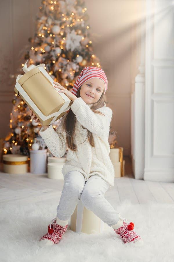 Den vertikala ståenden av det ljuva lilla kvinnliga barnet i vitkläder och värme den stora närvarande asken för sockahåll, mottar royaltyfria bilder