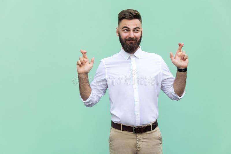 Den very listiga affärsmannen och att korsa fingrar för bra lycka och att hoppas önska ska komma riktigt och att se upp slugt royaltyfri foto