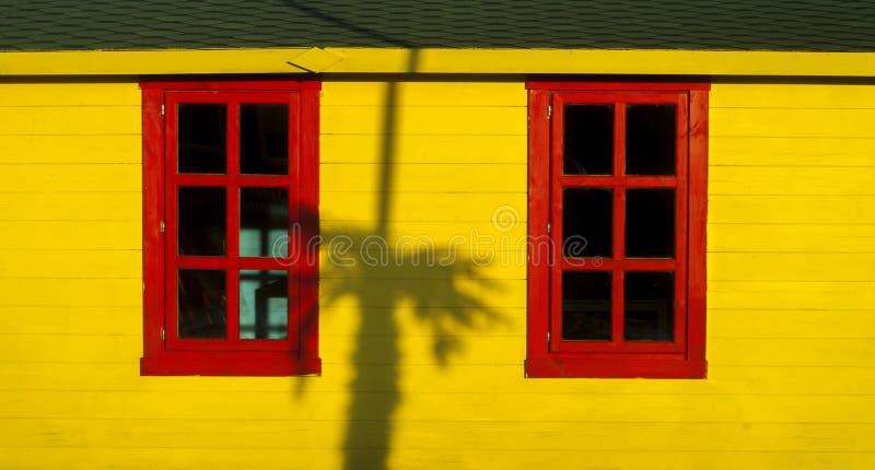 Den vibrerande röda fönsterramen i en gul vägg och gömma i handflatan skuggor arkivbild