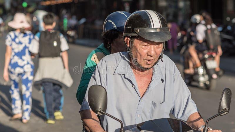 Den vietnamesiska äldre mannen kör en moped royaltyfri bild