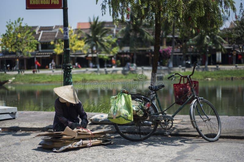 Den vietnamesiska kvinnan väljer upp papp för återanvändning på hennes cykel arkivfoto