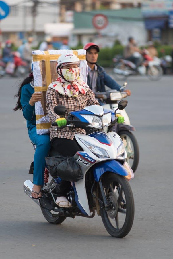 Den vietnamesiska motorcyklisten kör den rektangulära packen arkivbild