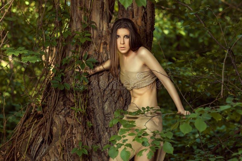 Den vilda flickan ser ut bakifrån ett träd arkivbilder