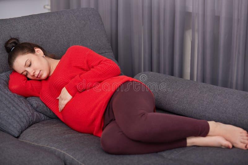 Den vilsamma europeiska kvinnan i rött förkläde och damasker, ligger barfota på soffan, håller handen på den svullna magen som gå arkivfoto