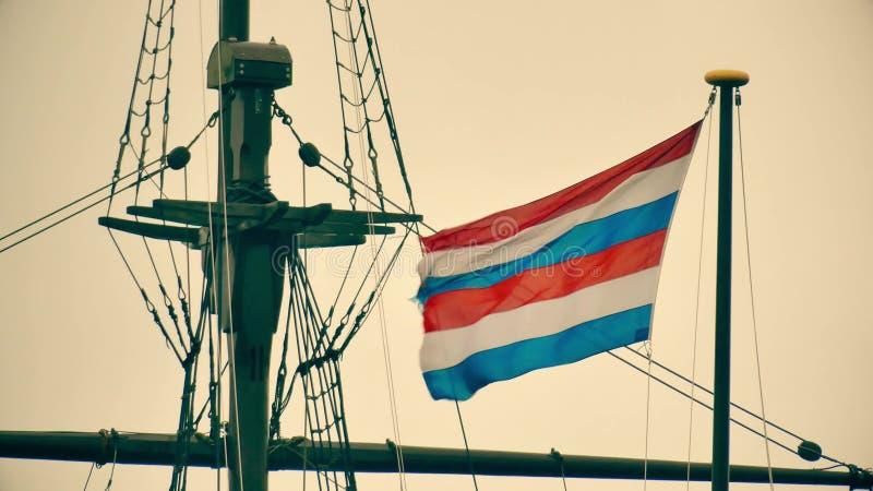 Den vinkande marinflaggan av sekreteraren av försvar av Nederländerna på masten av ett gammalt sänder minnesmärken i Amsterdam arkivfoto