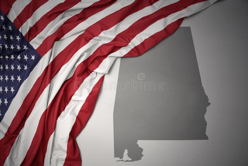 Den vinkande nationsflaggan av USA på en grå färgalabama stat kartlägger bakgrund arkivfoto
