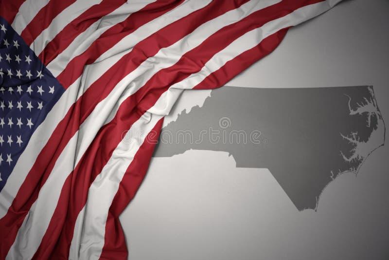 Den vinkande nationsflaggan av USA på en grå färgNorth Carolina stat kartlägger bakgrund royaltyfria foton