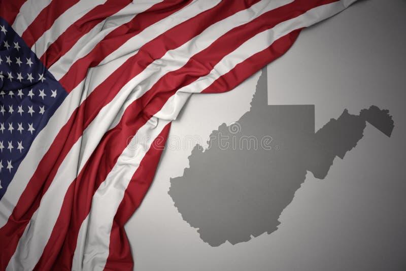 Den vinkande nationsflaggan av USA på en grå färgWest Virginia stat kartlägger bakgrund royaltyfria foton