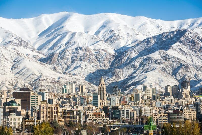 Den vinterTeheran sikten med en snö täckte Alborz berg royaltyfri bild