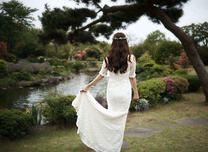 Den violetta buketten rymde i händer av en kvinna i den vita klänningen i ett damm med sörjer stramt trädet i Camellia Hill av de royaltyfria bilder