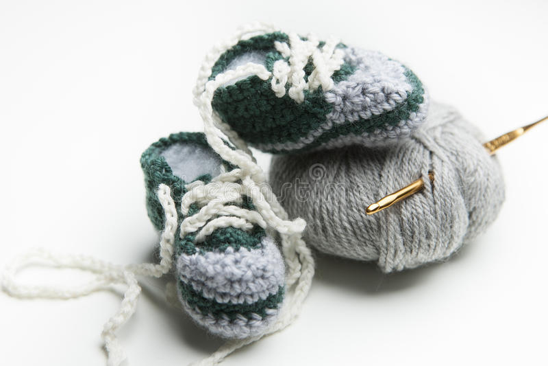 Den virkade handen behandla som ett barn skor med ull fotografering för bildbyråer
