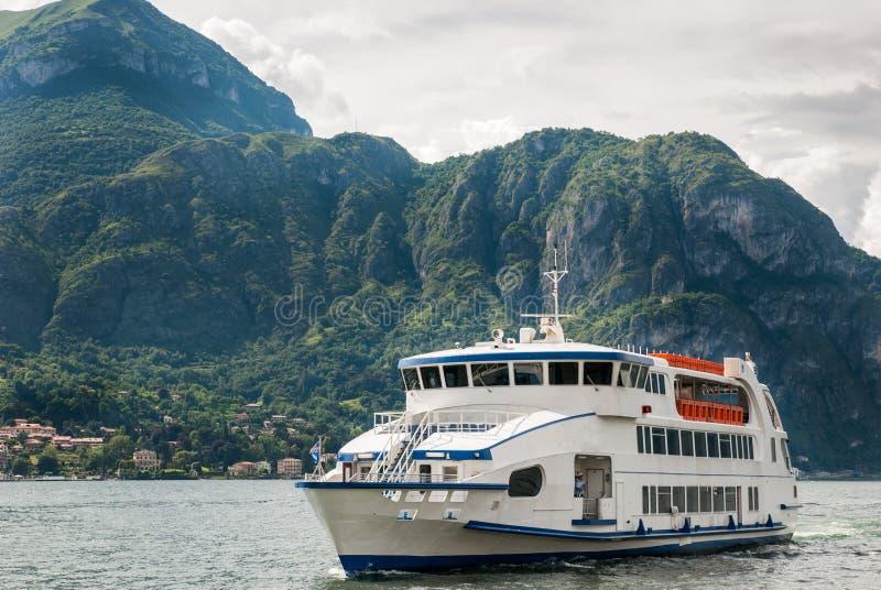 Den vita bilen och passagerarfärjan på sjön Como royaltyfria foton