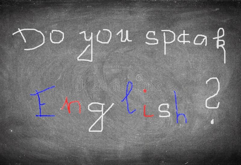 Den vita, blåa och röda inskriften talar du engelska? på den gamla svarta svart tavlan arkivbild
