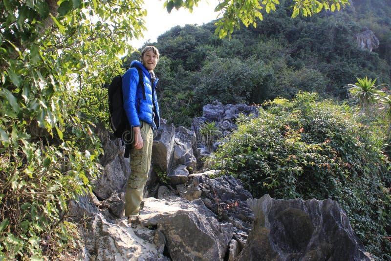 Den vita blonda manliga turisten i ett bl?tt omslag p? vaggar i Vietnam fotografering för bildbyråer