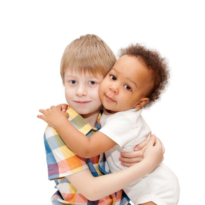 Den vita brodern som kramar svart, behandla som ett barn systern royaltyfri foto