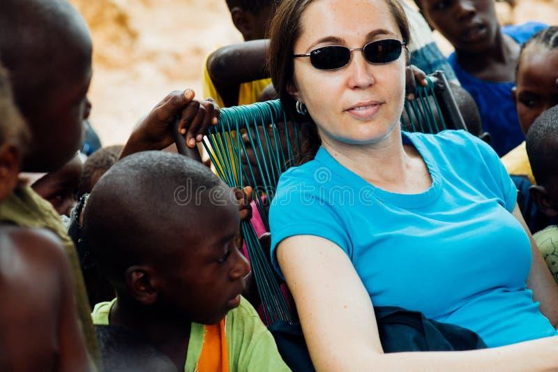 Den vita caucasian unga kvinnan spelar med folk för den svarta afrikanen i en lantlig by arkivbild