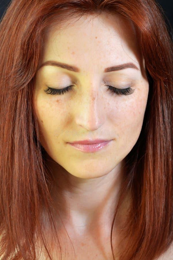 Den vita flickan med rött hår och gröna ögon med ögonfransförlängningar på mörk bakgrund med ögon stängde sig arkivbild